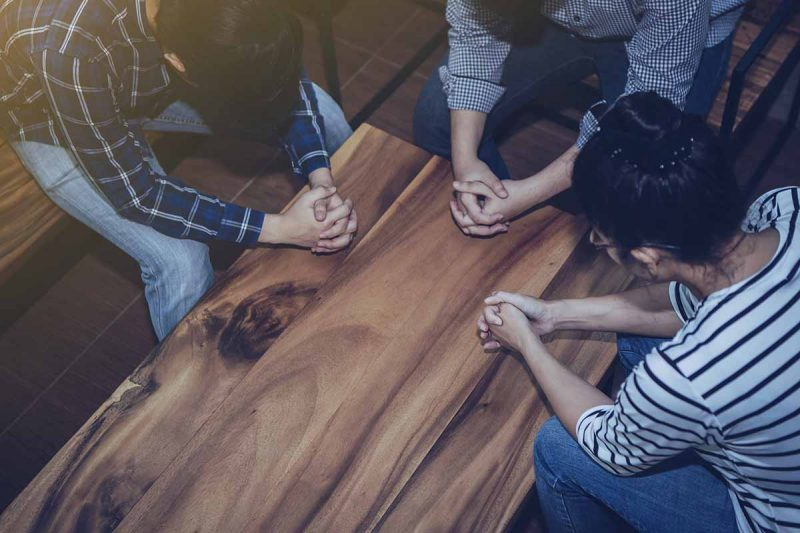 Christian people prays together around wooden table. prayer meeting
